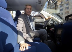 Vincent Bollore poses in an electric car